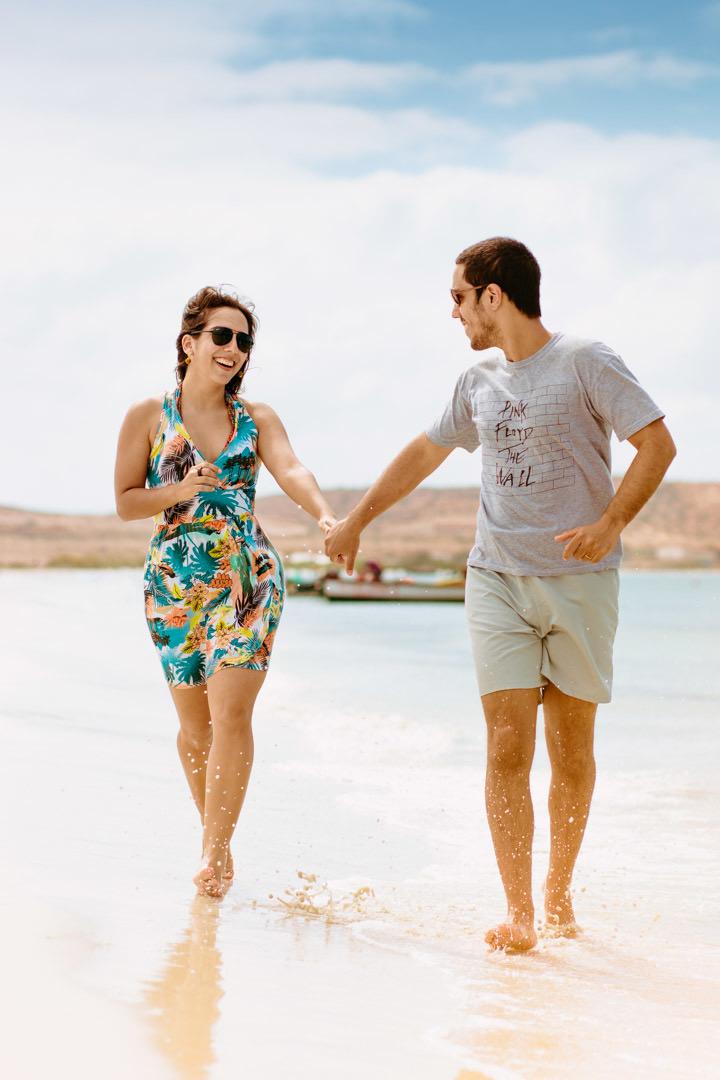 Ensaio dos casal na praia eles correndo na beira da praia