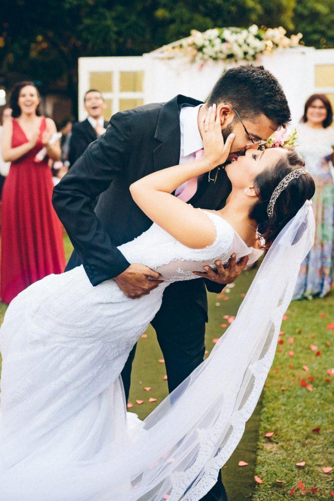 Casamento no campo Camila & Danilo um beijo do noivo segurando a noiva inclinando-a na saída da cerimonia ao ar livre