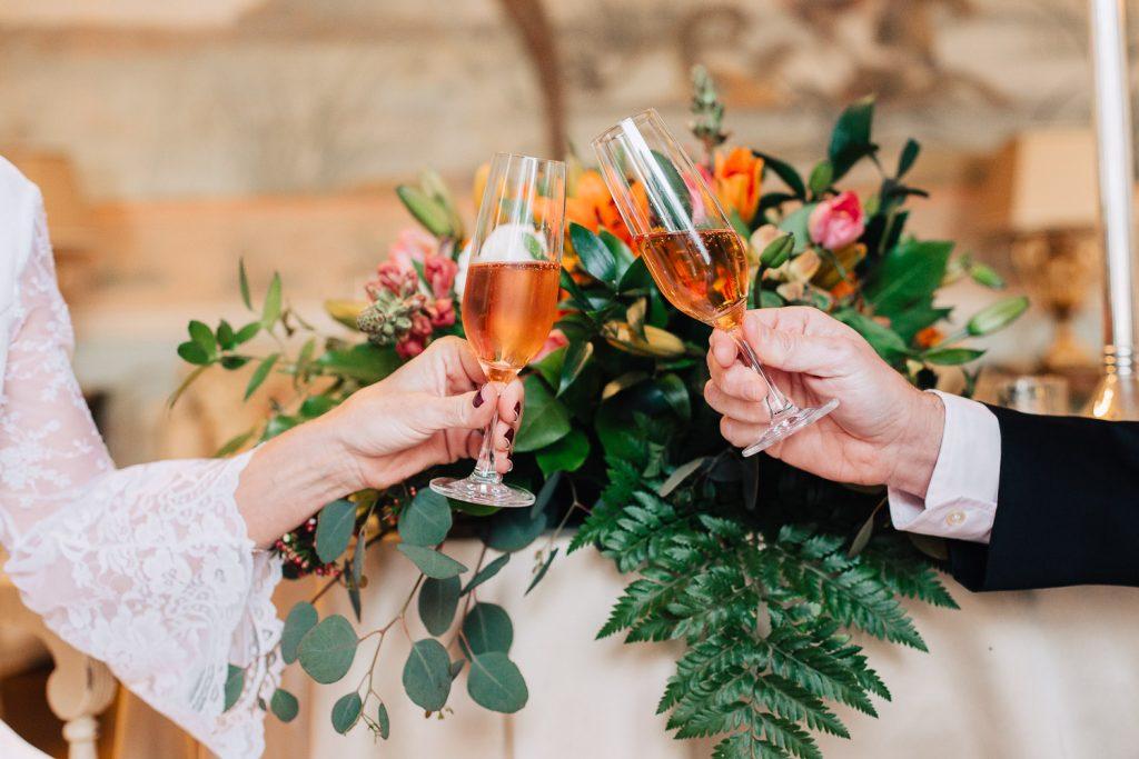 detalhe das mãos dos noivos segurando o champagne