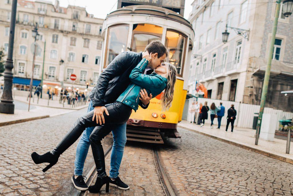 casal se beijando na frente de um bondinho na Praça da Figueira